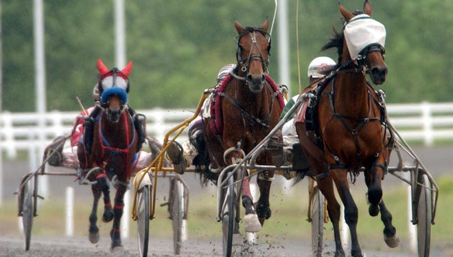 Horses race around the track at Vernon Downs.