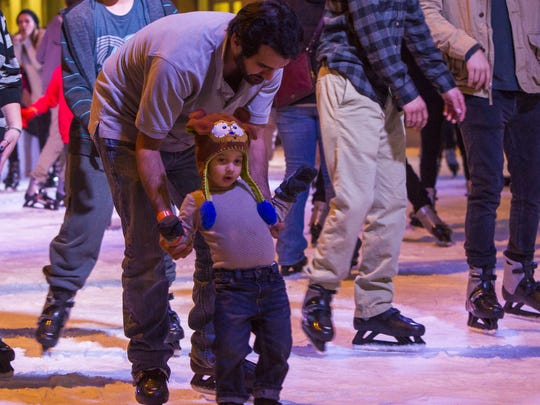 Michael Madril teaches his son Alex how to skate at the CitySkate Holiday Ice Rink in downtown Phoenix on Dec. 4, 2015.