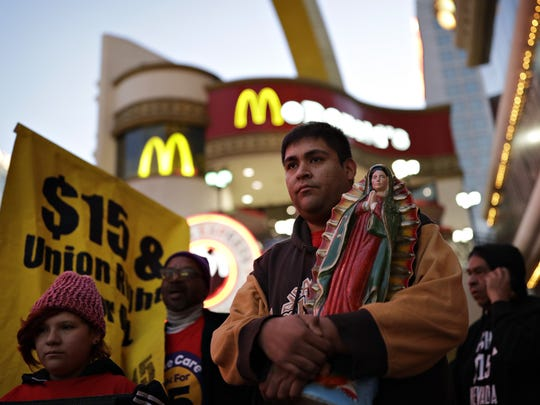 File photo: Martin Macias-Rivera holds a statue as he and others protest for a $15 wage near a McDonald's restaurant along the Las Vegas Strip, Tuesday, Nov. 29, 2016.