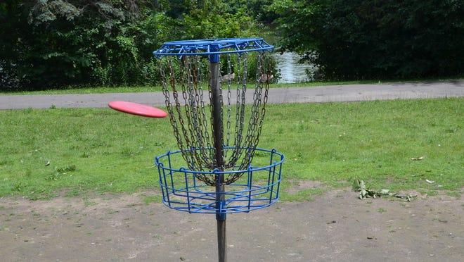 A disc flies into the basket at Battle Creek's Irving Park.