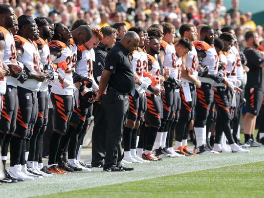 The Cincinnati Bengals lock arms during the national anthem before the Week 3 NFL football game between the Cincinnati Bengals and the Green Bay Packers, Sunday, Sept. 24, 2017, at Lambeau Field in Green Bay, Wisconsin.