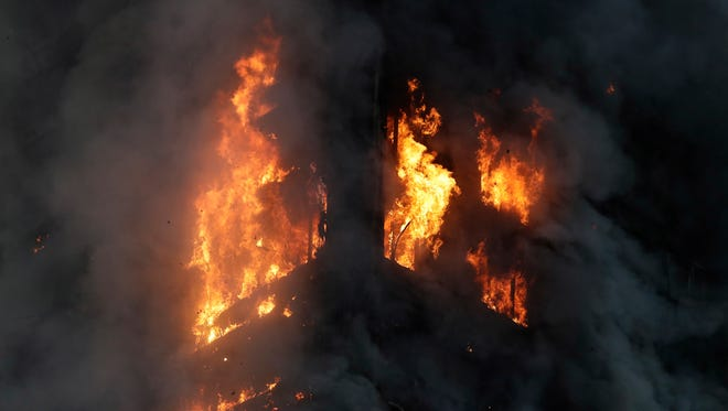Smoke and flames rise from a high-rise building on fire in London, Wednesday, June 14, 2017.