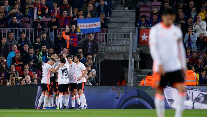 Valencia's players celebrate embracing their team mate Eliaquim Mangala scored a goal during the Spanish La Liga soccer match between FC Barcelona and Valencia at the Camp Nou stadium in Barcelona, Spain, Sunday, March 19, 2017. (AP Photo/Manu Fernandez)