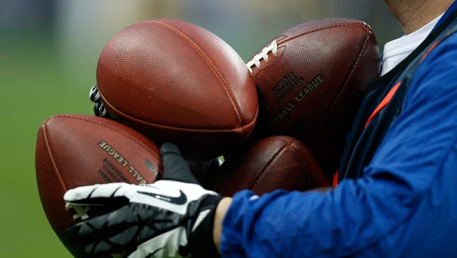 An official holds several footballs.