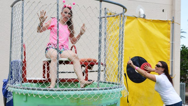 PAL dance contestant Michelle Leckenbusch about to be dunked by fellow PAL dance contestant Annette Strothers at the Family Pig Roast fundraiser.
