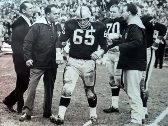 A photo of Wayne Hawkins being helped off the field after suffering an injury while playing for the Raiders. Photo taken in Rancho Mirage on Thursday, December 14, 2017. Hawkins suffers from brain trauma and his insurance from the NFL is running out despite needing around the clock care. To the left of the photo is Al Davis, head coach of the Raiders from 1963 to 1965 and later managing general partner of the team.