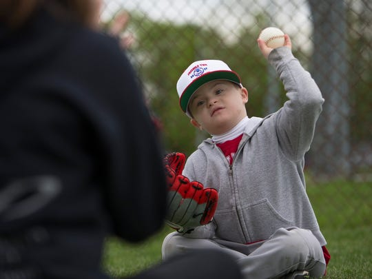Bobby Marshall, 7, of Howell, plays catch with a volunteer.