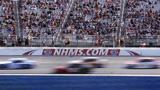 Cars steer through Turn 1 as fans watch in 2017 during the NASCAR Cup Series 301 auto race at New Hampshire Motor Speedway in Loudon, N.H. New Hampshire Motor Speedway will allow a limited number of fans in the grandstands and suites for the Aug. 2, 2020 NASCAR Cup Series race.  Fans will be subject to social distancing requirements and additional health and safety protocols.
