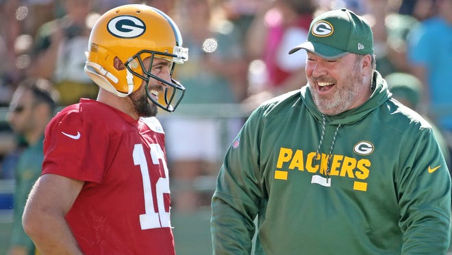 Green Bay Packers quarterback Aaron Rodgers (12) listens as head coach Mike McCarthy tells a funny story during Green Bay Packers Training Camp Saturday, July 29, 2017 at Ray Nitschke Field in Ashwaubenon, Wis.