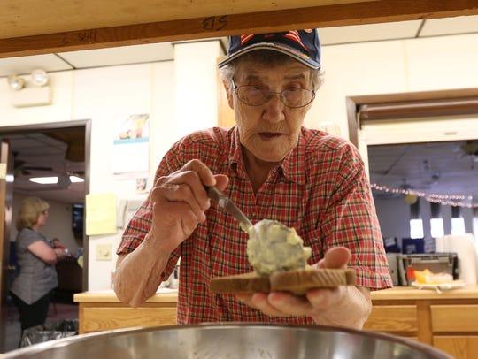 Lorraine Bentzler, 83, scoops egg salad onto bread