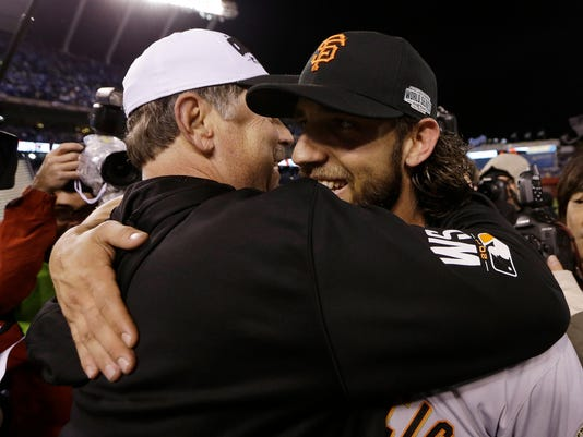 San Francisco Giants manager Bruce Bochy and Madison Bumgarner celebrate after Game 7 of baseball's World Series against the Kansas City Royals Wednesday, Oct. 29, 2014, in Kansas City, Mo. The Giants won 3-2 to win the series. (AP Photo/David J. Phillip)