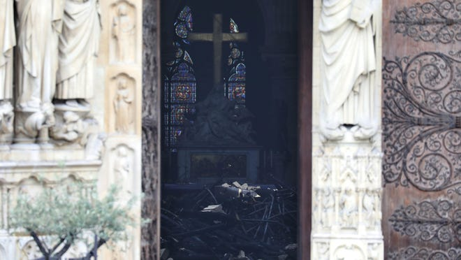 Charred debris inside Notre Dame cathedral is visible to passersby Tuesday April 16, 2019. Firefighters declared success Tuesday morning in an over 12-hour battle to extinguish an inferno engulfing Paris' iconic Notre Dame cathedral.