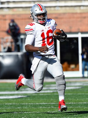 Nov 14, 2015; Champaign, IL, USA; Ohio State Buckeyes quarterback J.T. Barrett (16) carries the ball against Illinois Fighting Illini during the second quarter at Memorial Stadium. Mandatory Credit: Mike DiNovo-USA TODAY Sports