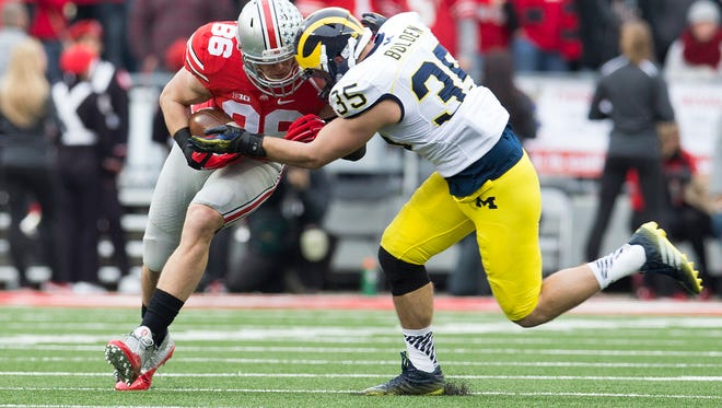 Ohio State Buckeyes tight end Jeff Heuerman is hit by Michigan Wolverines linebacker Joe Bolden at Ohio Stadium in November of 2014.