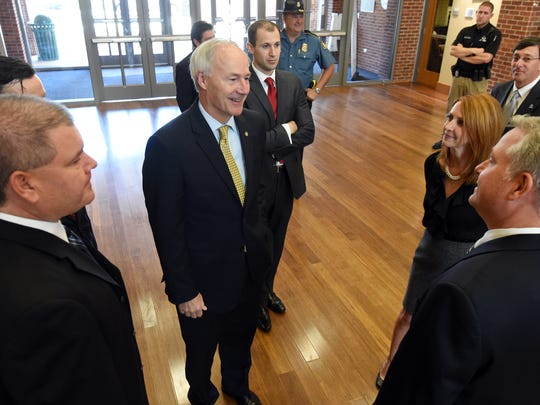Gov. Asa Hutchinson talks with representatives with Baxter International at Arkansas State University Mountain Home on Thursday. Hutchinson was on hand for the announcement of 225 new jobs at Baxter International in Mountain Home.