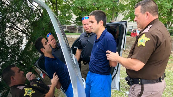 Sheriff Ray Dudley (right) and Chief Deputy David Spence II prepare Marco Contreras-Desilva for transport to the Delaware County Justice Center on Friday, when  the Muncie man was captured after leading narcotics investigators and deputies on a foot chase.