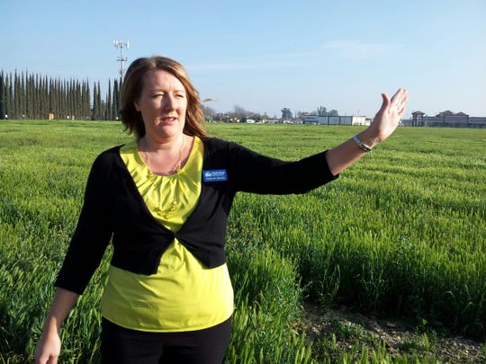 Betsy McGovern-Garcia, program director over real estate development for Self-Help Enterprises, stands in front of the five-acre vacant lot in northeast Visalia where her organization wants to build 36 apartments for low-income families in this Feb. 2015 file photo.