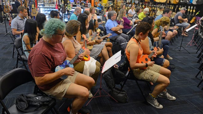 Beginning ukulele players get into the music Saturday morning during the free beginning ukulele lessons at Blues Angel Music.