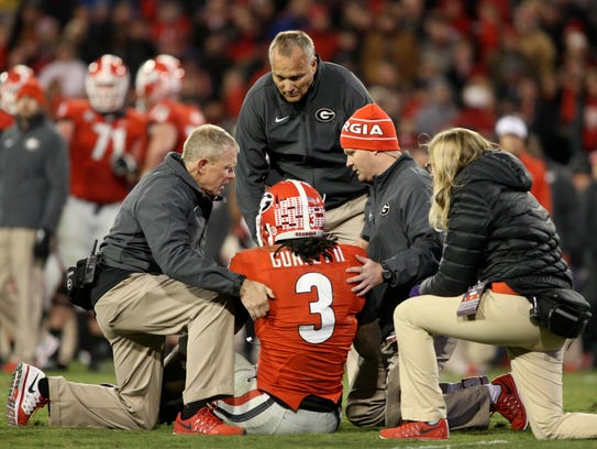 Georgia's Todd Gurley is cared for by trainers and