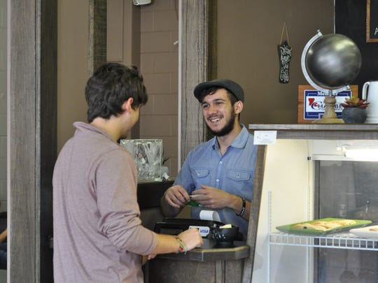 Louisiana College junior Chris Verzwyvelt, 20, serves a customer, and fellow classmate, Wednesday. Verzwyvelt is the new owner of Hidden Grounds in Pineville, formerly known as The Coffee Shop.