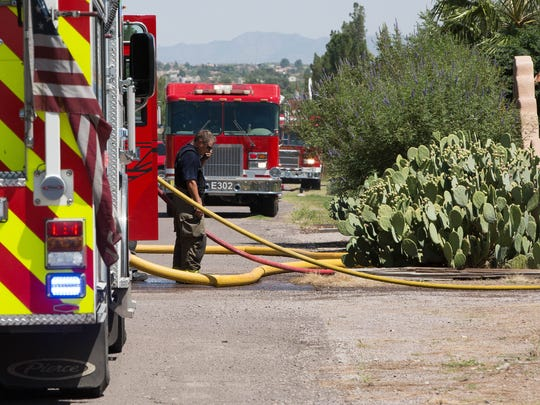 Firefighters from Doña Ana County work to put out a fire that demolished a shed and carport on King Edwards Avenue, north of Las Cruces, on Monday September 11, 2017.