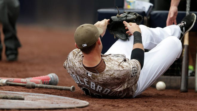 San Diego Padres third baseman Will Middlebrooks stays down after injuring himself while trying to chase down a foul ball hit by the Arizona Diamondbacks' Cliff Pennington during the seventh inning of a baseball game Sunday, June 28, 2015, in San Diego.