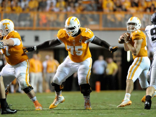 In this Aug. 31, 2014, photo, offensive linemen Mack Crowder, left, and Marcus Jackson provide pass protection for quarterback Justin Worley during a 38-7 win over Utah State in Knoxville, Tenn. After allowing 30 sacks in Tennessee's first seven games, the Volunteers have yielded only two sacks over their last two contests. (AP Photo/Knoxville News Sentinel, Michael Patrick)