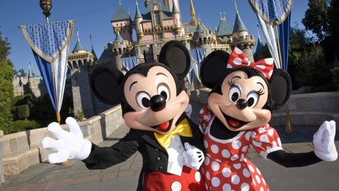 Mickey and Minnie Mouse greeting visitors to Disneyland.