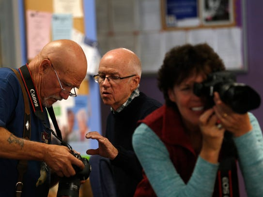 San Juan College photography instructor Tony Bennett works with student Bill Nourse, left, and Dawn Smith, right, on Thursday during Bennett's intermediate digital photography class portraiture exercise at the Bloomfield Senior Center.