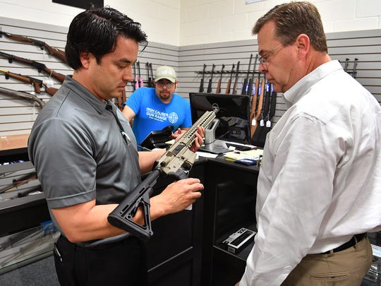 Clint Blowers, left, and Nick Colarelli check out an AR-15 rifle with the help of sales associate Rolando Alvarado, center, during the grand opening of High Caliber Indoor Gun Range Friday morning. The business is just north of the city limits on I-44.