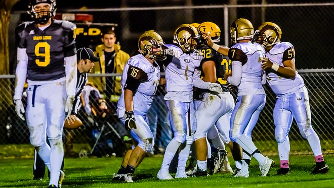 Teammates celebrate with Khari Gray ,1, of Holt after his touchdown reception put the Rams up 29-7 over undefeated Grand Ledge with 10:55 remaining in the 4th quarter of their game Friday October 21, 2016 in Grand Ledge.  KEVIN W. FOWLER PHOTO