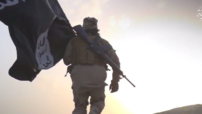 An image from an Islamic State propaganda video features an ISIS fighter with an M-16 rifle and ISIS flag. A West Palm Beach man pleaded guilty Friday to conspiring to provide support to ISIS.