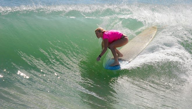 Surfer Eva Porter ducks under the lip on her longboard during the 2014 Salty Sweet Pro/Am Surf Contest.