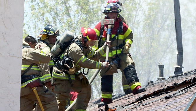 El Paso firefighters open a hole in the attic space of a duplex while extinguishing a fire on May 30 in the 3200 block of Isla Bahia Way in East El Paso.