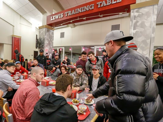 In this Jan. 19, 2017, photo, a magician performs card tricks at the Lewis Training Table facility at the University of Nebraska in Lincoln, Neb., where athletes can dine on specially made entrees such as mahi mahi steaks, bison meatloaf or chicken marsala. The hundreds of millions of dollars that have poured into the Power Five conferences, much of it from television rights fees, have enriched dozens of schools and allowed them to give their athletes the best of everything, right down to what they eat every day. (AP Photo/Nati Harnik)