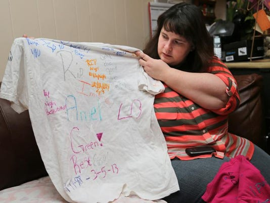Danielle Green shows a T-shirt Monday that was among items left in a memorial to her late daughter, Angel, 14.