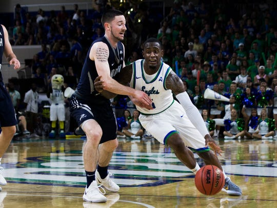 Florida Gulf Coast University guard Zach Johnson (5) dribbles the ball against a defender during the ASUN tournament semifinal game against North Florida at Alico Arena on Thursday.