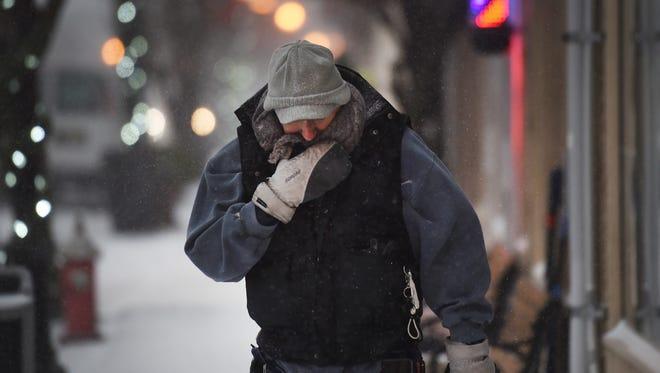 A man muffles himself against the wind and snow as he walks along  Fair Lawn Avenue as wind blows snow in Fair Lawn on 01/04/18.
