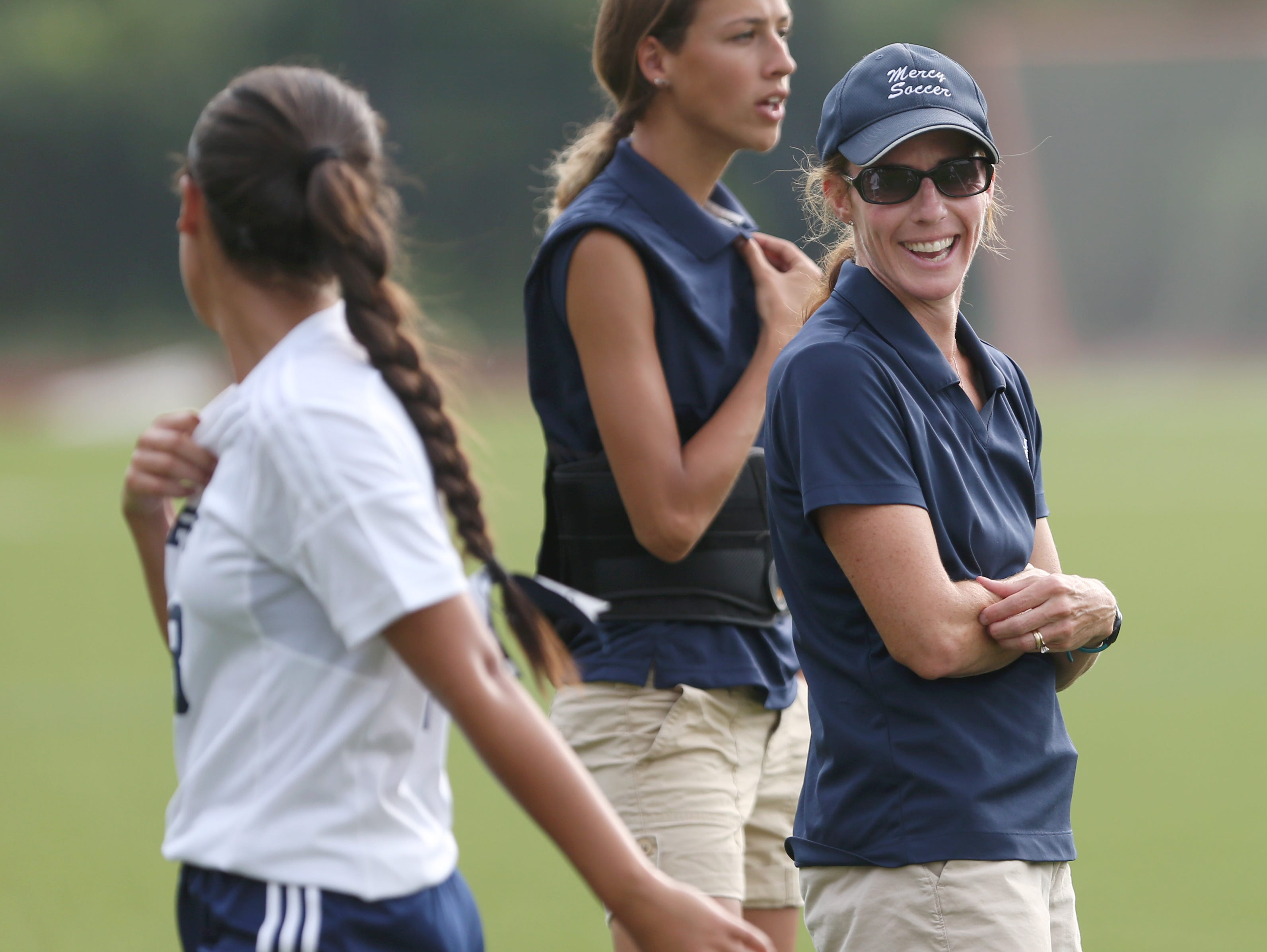 Donna Trost, head coach of Mercy varsity girls soccer, shares a laugh with her player, Olivia Torres, as Torres leaves the field during Mercy's matchup against Aquinas at Mercy High Tuesday, Sept. 8, 2015 in Brighton. Trost is the latest winner of the Democrat & Chronicle Coaches Who Care award.