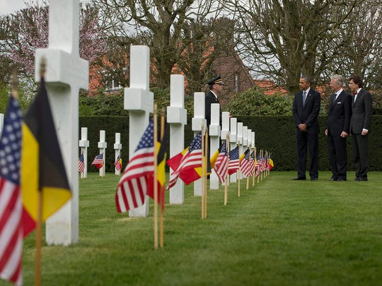 Chris Arsenaeult, left, speaks to President Obama, Belgian King Phillipe and Belgian Prime Minister Elio Di Rupo during a walk through the American cemetery at Flanders Field in Waregem, Belgium. The World War I cemetery contains the remains of 368 U.S. military personnel.