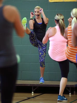 Julie Voris appeared in the popular P90X workout videos and has workout videos of her own. Here she teaches her class at the YMCA in Fishers.