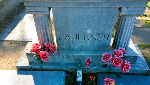 "This March 12, 2017 photo shows the grave of novelist William Faulkner in Oxford, Miss. Fans sometimes leave liquor bottles at the site. An exhibit at Rowan Oak, the house where Faulkner lived in Oxford, says he was a ""notorious binge drinker."""
