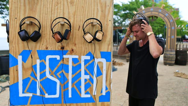 Artist Jonathon Kingsbury listens for music as he sets up his art installation that will allow up to 12 people to listen to music for the 2015 Forecastle Festival that starts Friday and runs through Sunday.  July 15, 2015