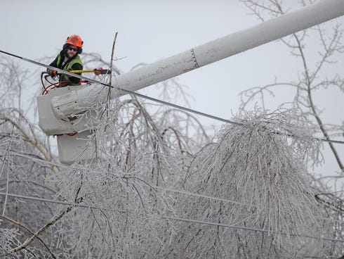 Andrew Powers, an arborist with Asplundh Tree Experts, clears iced branches from power lines along Mayflower Heights Drive in Waterville, Maine, on Dec. 23, 2013.