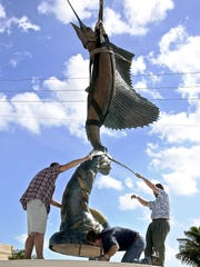 Jason Kresser (from left), Jeanann Paulus, Jim Paulus and Geoffrey Smith attempt to secure the 3,000 pound sailfish sculpture in the center of Sailfish Circle in September 2003. Kresser of Tequesta was Smith's apprentice and the Pauluses were from the Eagle Bronze Foundry and Gallery in Wyoming.