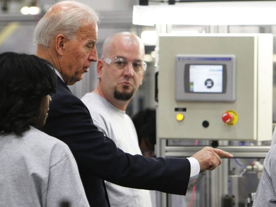 Vice President Joe Biden asks a question of Roy Blessinger, center, an employee of the Ener1 plant in Greenfield, Ind., that produces advance lithium ion batteries for the Think City electric car going into production in Elkhart. Biden toured the plant on Wednesday, Jan. 26, 2011.