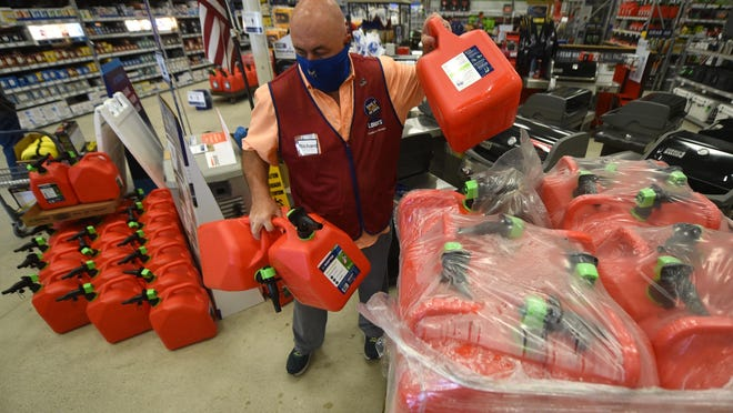 Richard Corbett unloads gas cans while adding to the hurricane-related supplies at Lowe's in Wilmington on Friday.