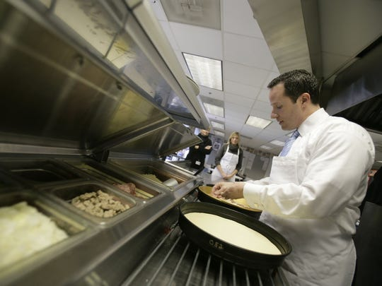 Chris Ilitch, CEO of Ilitch Holdings, makes a pizza in the test kitchen of Little Caesars Pizza Co. at the company's headquarters in downtown Detroit in December 2005.