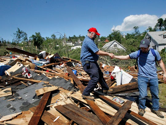 Shawn Menard, right, reaches to help homeowner Tony