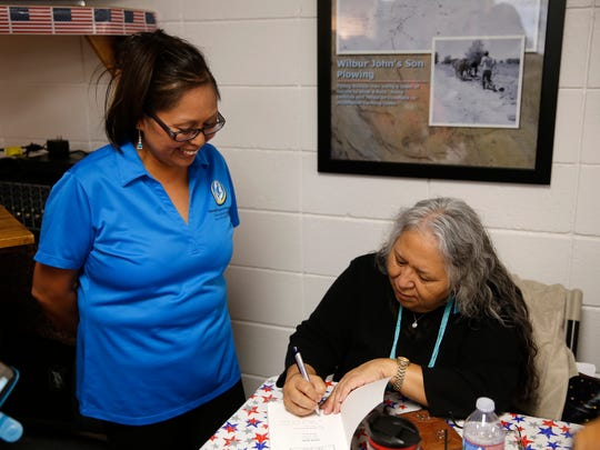 """Denise Yazzie gets her copy of """"Her Enemy, Her Love"""" signed by author Evangeline Parsons Yazzie on Friday at the Farmington Indian Center."""